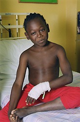 Young patient with bandaged hand sitting on bed on Children's medical ward,