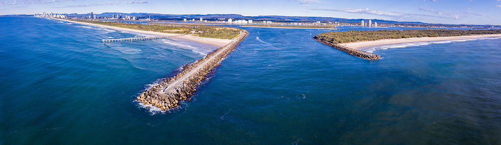 Panoramic aerial view of Gold Coast Seaway & Sand Pumping Jetty, Surfers Paradise skyline in distance, The Spit, Gold Coast, Queensland, Australia