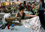 HANGZHOU, CHINA - 4 August 2005 - A factory worker sews Chinese silk for export in Hangzhou.