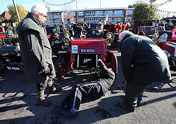 Participants in the Bonhams London to Brighton Veteran Car Run tends to their cars during a stop in Crawley, Sussex.
