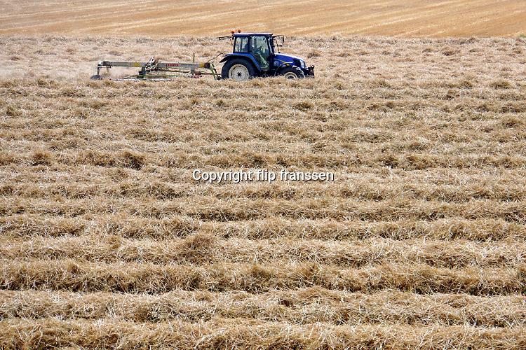 Nederland, Kekerdom, 1-8-2019 Een boer in de Ooijpolder rijdt met een trekker door het restafval van de graanoogst. Het wordt gebruikt als stro . Dit kan op verschillende manieren gebruikr worden. Een ervan is als ondergrond in de stal waarna het na vermengd te zijn met uitwerpselen, vruchtbare stalmest wordt. Bij het maaidorsen van graan blijven de plantenstengels met de uitgedorste aren achter op het land. Deze worden tot grote ronde balen opgerold of tot rechthoekige strobalen, stropakken samengeperst. Ook wordt meer en meer stro ondergeploegd. Foto: Flip Franssen