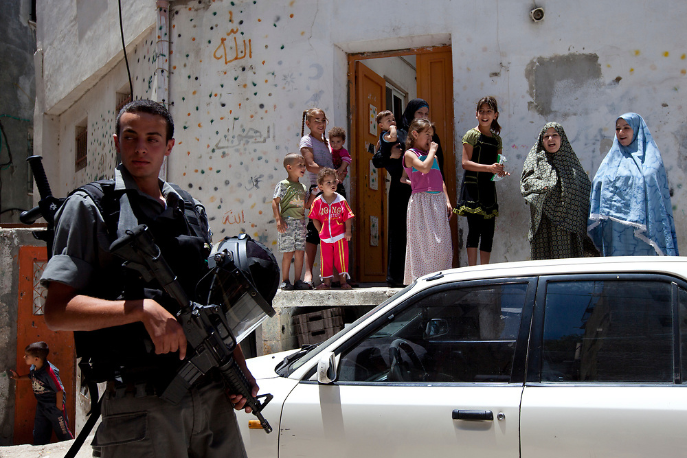 Members of a Palestinian family watch as an Israeli border policeman patrols in the east Jerusalem neighborhood of Silwan, during a visit by the Israeli parliament committee for the children's rights to houses of Jewish families residing in a mostly Palestinian area, on July 6, 2010.