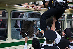London, UK. 31st August, 2021. Metropolitan Police officers climb onto a vintage bus used by environmental activists from Extinction Rebellion to block a road junction to the south of London Bridge on the ninth day of their Impossible Rebellion protests. Extinction Rebellion are calling on the UK government to cease all new fossil fuel investment with immediate effect.