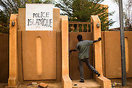 A man tries to enter a Islamic Police station where Malian jihadists disciplined the local population for smoking, talking to women, or not wearing hijab.