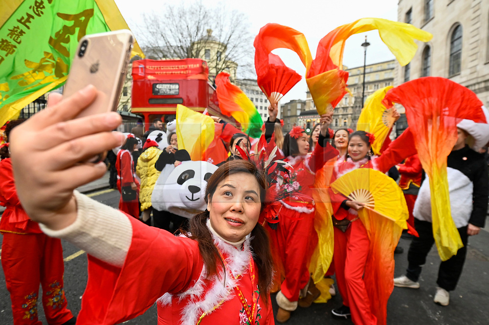© Licensed to London News Pictures. 26/01/2020. LONDON, UK.  Participants in traditional costume take a selfie ahead of a parade as part of the Chinese New Year celebrations in Chinatown to celebrate the Year of the Rat.  Chinese New Year in the capital draws hundreds of thousands of Londoners and tourists and is the biggest such celebration outside Asia.  This year's event takes place in the shadow of an outbreak of the coronavirus in Wuhan, China, which has so far claimed the lives of 56 people.  Photo credit: Stephen Chung/LNP