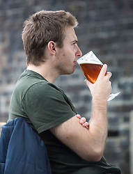 © Licensed to London News Pictures. 04/07/2020. London, UK. A young man enjoying a pint of beer at The Ice Wharf pub at Camden Lock, North London as Pubs, bars, cafes and restaurants are allowed to fully open for the first time since lockdown. Photo credit: Ben Cawthra/LNP