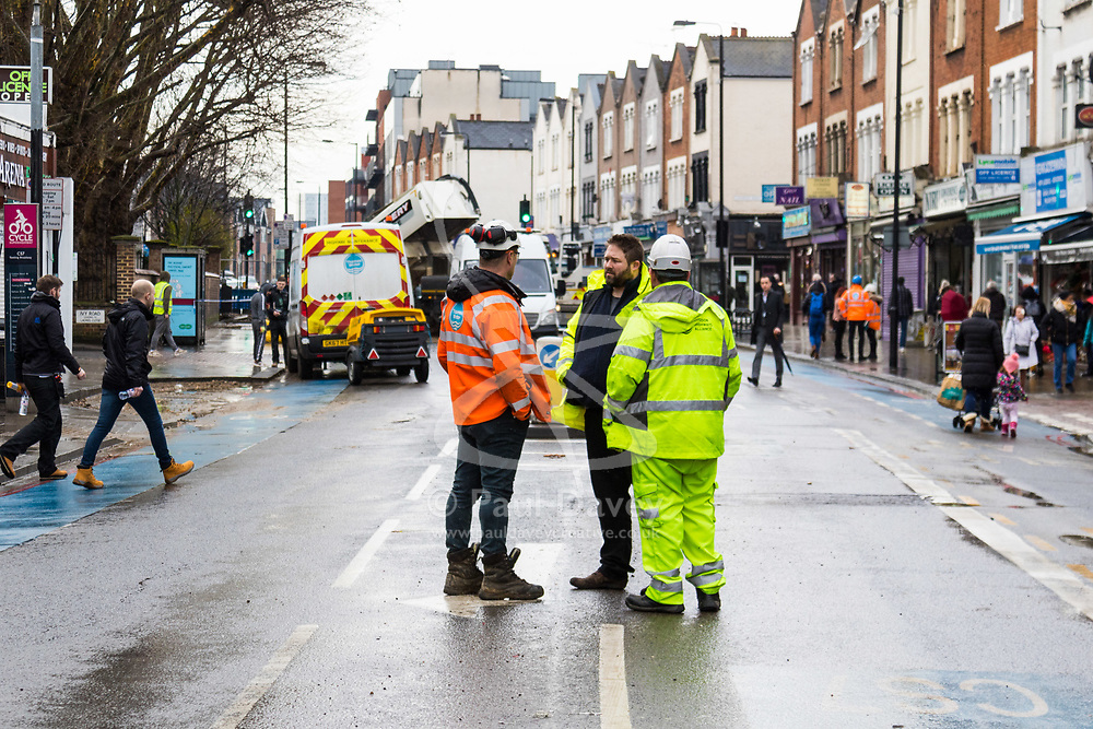 Workers clean up and prepare to dig up a large burst water main just yards from the entrance to Tooting Broadway station in South London. London water supply companies are battling a series of burst mains following the recent cold weather brought on by 'The Beast From The East'. London, March 07 2018.