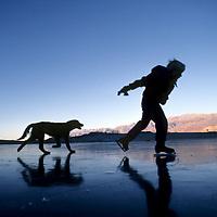 """ICE SKATING. 8-year old Ben Wiltsie (MR) skates with """"Khampa"""" on 5 Bridges pond. Owens Valley, CA."""