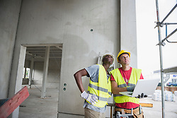 Construction workers with laptop at building site, Munich, Bavaria, Germany