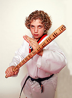 7 February 2008: 11 year old boy Quinn Stafford with long wooden stick weapon. Tae Kwon Do student athletes in motion. Young kids practicing Taekwondo at the USA Black Belt Academy in Huntington  Beach, CA. Tae Kwon Do is a Korean Martial Art discipline that trains the body and mind.  It is global sport that is an official Olympic sport. *Background Retouched *