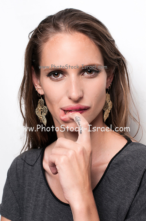 A hip and trendy young woman with SUCCESS tattooed on her index finger on white background Model release available