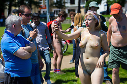 © Licensed to London News Pictures. 08/06/2014. BRIGHTON, UK. A nude protester reacting to people who filming her by filming them as cyclists protesters getting ready to cycle through the streets of Brighton on Sunday 8 June 2014 as part of the World Naked Bike Ride, which aims to raise awareness of cyclists on the roads and in the traffic. Photo credit : Tolga Akmen/LNP