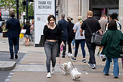 After the announcement that Covid rules are to be relaxed by the government on July 19th, a woman crosses Oxford Circus with two pet dogs in the West End, on 8th July 2021, in London, England.