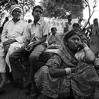 Residents of Bhadaura village in Masauri block, Patna District listen to a talk about polio by  Akhilesh Singh, BMC (Block Mobilisation Coordinator). The village has a large population working as day-wage farm labourers so Singh urged them to be at home during the immunisation round. The village is dominated by Ravidas and Paswan castes (both low caste polio affected) together with some Brahmins...Photo: Tom Pietrasik.Patna District, Bihar, India..November 6th 2006