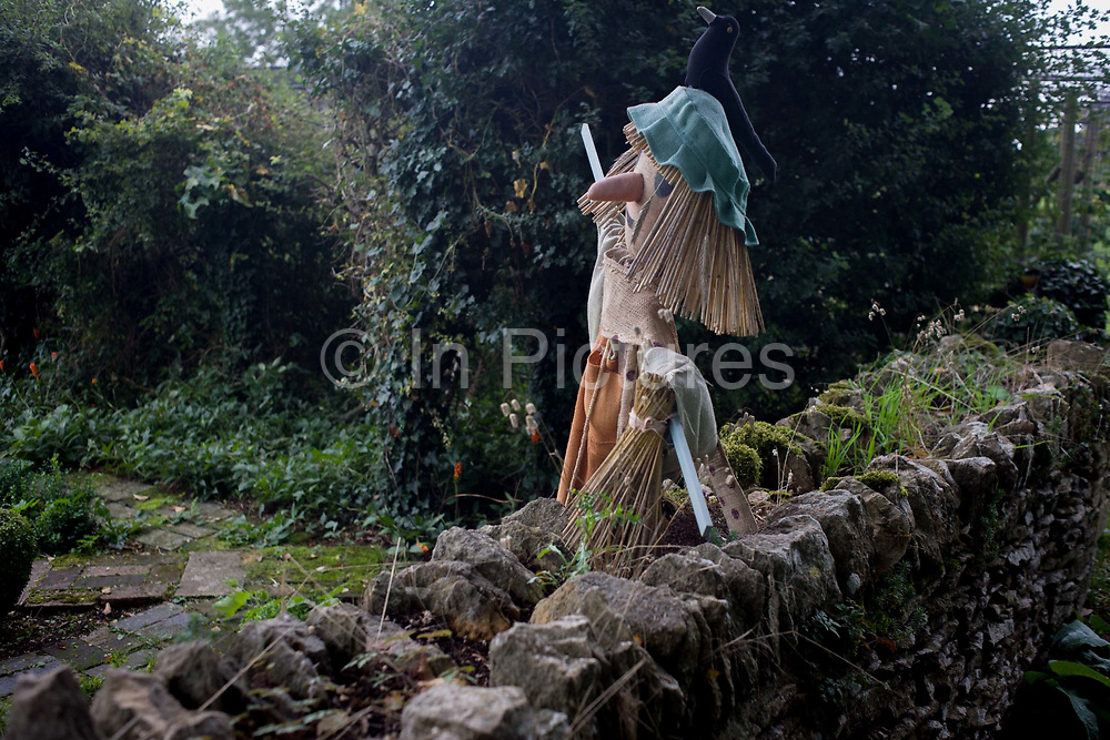 A scarecrow guards crops and plants by a Gloucestershire country garden dry stone wall. The human figure has been made of straw and fabric, a cloth hat and the form of a blackbird on its head. It stands against the stone wall at the boundary of land in this Cotswold garden, near Cirencester. A scarecrow or hay-man is a decoy or mannequin in the shape of a human. It is usually dressed in old clothes and placed in open fields to discourage birds such as crows or sparrows from disturbing and feeding on recently cast seed and growing crops. As its name suggests, it scares away crows (and other species) from a field.
