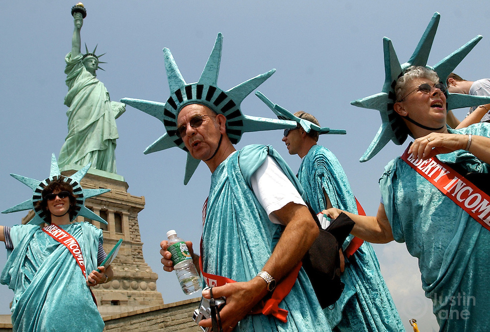 Tourists dressed up as the Statue of Liberty visit monument on the day it was partially reopened to the public.