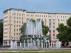 Ornate GDR era fountain and apartment buildings on Karl Marx Allee in Berlin