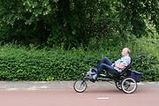 Een man rijdt op een aangepaste ligfiets door Utrecht.<br /> <br /> A man is riding a special recumbent bike in Utrecht.