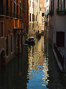 Gondola in a narrow Venice canal with reflections in the water