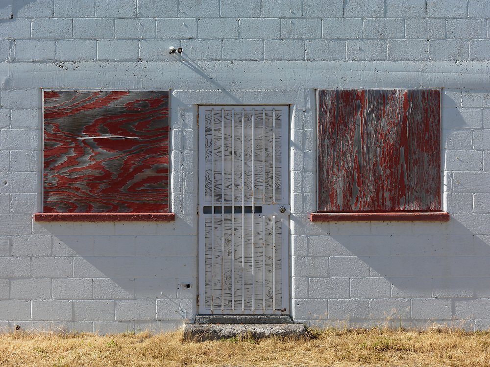 Editions of 8<br /> Boarded windows and locked door on white cinder block building roadside in Eastern Idaho