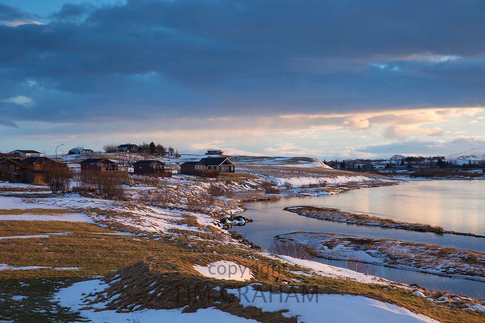 Sun rising over luxury wooden holiday homes overlooking River Ranga in typical Icelandic landscape in Hella, South Iceland
