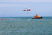 A crew member from HM Coastguard rescue helicopter G-C1JW  attempts to land onto the back of the Royal National Lifeboat Institution RNLI Dover Life boat 17-09 during a training exercise in the sea just outside Folkestone Harbour, Folkestone, Kent. UK.