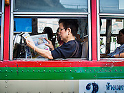 04 FEBRUARY 2015 - BANGKOK, THAILAND: Passengers on a bus on Phloen Chit Road in Bangkok. After months of relative calm following the May 2014 coup, tensions are increasing in Bangkok. The military backed junta has threatened to crack down on anyone who opposes the government. Relations with the United States have deteriorated after Daniel Russel, the US Assistant Secretary of State for Asian and Pacific Affairs, said that normalization of relations between Thailand and the US would depend on the restoration of a credible democratically elected government in Thailand.    PHOTO BY JACK KURTZ