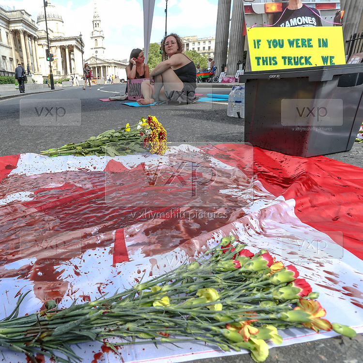 """A blood-stained Canadian flag lays beside the protestors. """"This act of civil disobedience is to condemn the Canadian government's complicity in the death last Friday"""" activists said. <br /> Further, after the flag stained in blood two activists are seen to have chained themselves in the middle of the street facing the entrance of the Canada House.<br /> Dozens of Canadian and British animal rights activists are protesting against a law brought by the Ontario government known as Bill 156. The law makes it illegal to take photographs of animals in transport to slaughterhouses and give water to animals before their death. (Photo/ Vudi Xhymshiti)"""