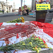 "A blood-stained Canadian flag lays beside the protestors. ""This act of civil disobedience is to condemn the Canadian government's complicity in the death last Friday"" activists said. <br /> Further, after the flag stained in blood two activists are seen to have chained themselves in the middle of the street facing the entrance of the Canada House.<br /> Dozens of Canadian and British animal rights activists are protesting against a law brought by the Ontario government known as Bill 156. The law makes it illegal to take photographs of animals in transport to slaughterhouses and give water to animals before their death. (Photo/ Vudi Xhymshiti)"
