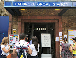 """People look at a sign at Labroke Grove Station in London, which says """"owing to the safety of the Tower"""" the lines had been partly suspended."""