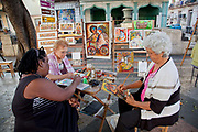 Elderley women painting in the street, at the outdoor art market on the Prado, Central street of Havana, Cuba.