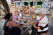 Elderley women painting in the street, at the outdoor art market on the Prado, Central street of Havana, Cuba.