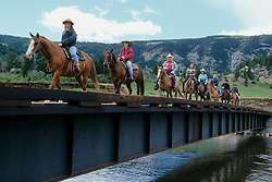 North America, United States, Montana, Boulder River Valley, group of riders crossing bridge on horseback