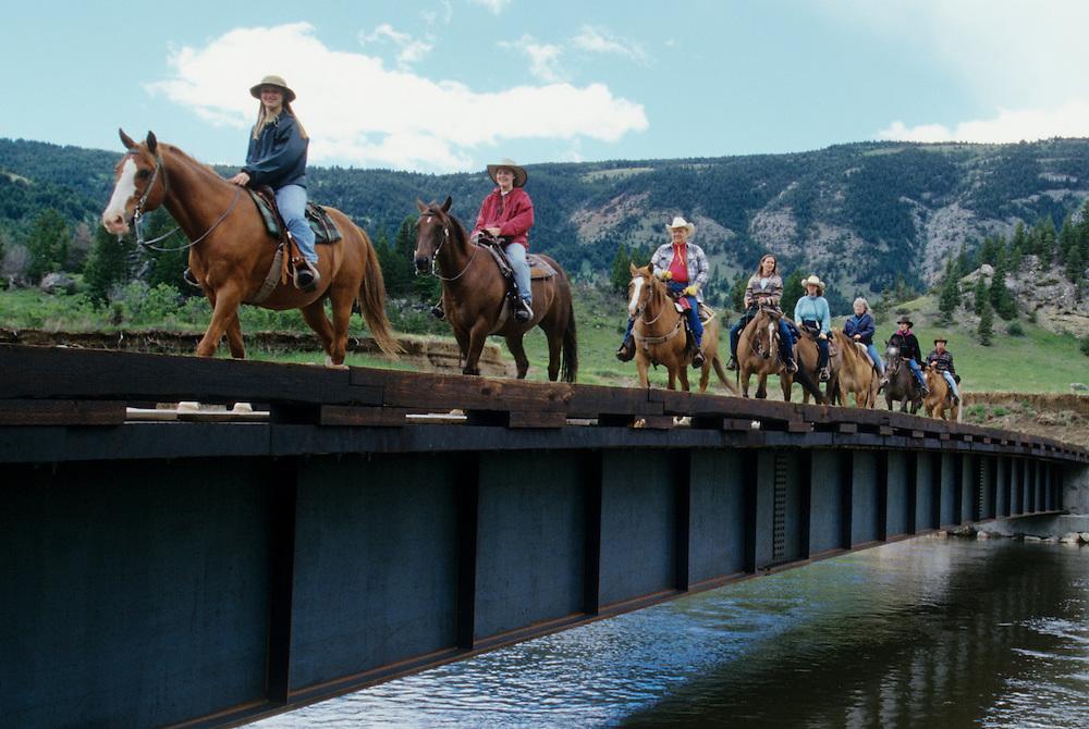 North America, United States, Montana, Boulder River Valley, group of riders crossing bridge on horseback