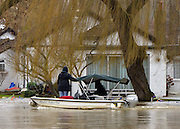 © Licensed to London News Pictures. 29/12/2012. Shepperton, UK The occupants of a boat check a house on Pharaoh's Island, Surrey, as it is surrounded by floodwater. Flooding along the River Thames today 29th December 2012. Forecasters say the UK can expect heavy rain and winds the coming days. Photo credit : Stephen Simpson/LNP