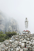 Virgin Mary statue in mountains on foggy day, Col de Bavella, Corsica, France