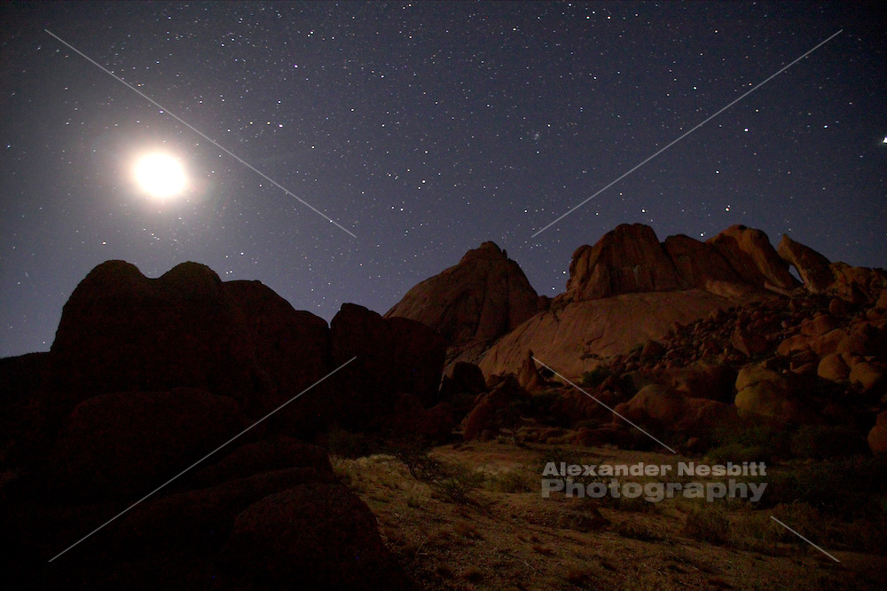 Spitzkoppe, the granite dome peak often called the Matterhorn of Namibia under a full moon on a clear, starry night.
