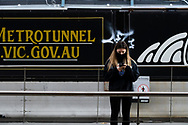 A woman in a mask waits for a tram near to Metro tunnel works on Flinders Street as the state waits to see if the lockdown will be extended as it enters 6th day of the state wide COVID-19 snap lockdown that has been placed on the State of Victoria.  (Photo by Michael Currie/Speed Media)
