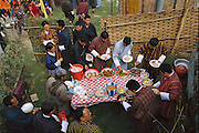 During a celebration of the first electricity to come to this region of Bhutan, visiting dignitaries join village member Namgay (in gray with blue cuffs at the table) at a buffet of red rice, potatoes, tomatoes, cucumbers, beef, chicken, and a spicy cheese and chili pepper soup. The villagers have been stockpiling food for the event. (Supporting image from the project Hungry Planet: What the World Eats.) The Namgay family living in the remote mountain village of Shingkhey, Bhutan, is one of the thirty families featured, with a weeks' worth of food, in the book Hungry Planet: What the World Eats.
