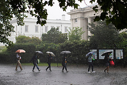 © Licensed to London News Pictures. 25/07/2021. London, UK. Members of the public shelter under umbrellas as they walk in Greenwich Park in South East London. An amber weather warning for thunderstorms is in place in parts of London and the South East . Photo credit: George Cracknell Wright/LNP
