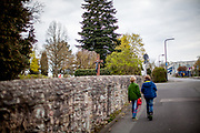 Two boys are walking beneath the church wall in Oberursel, Stierstadt.