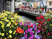 International flags fly over the River Arve and flower boxes in Chamonix, France, Europe.