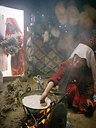 """Ustad Ghulam's wife cooking nan bread in the kitchen yurt..Campment of """"second"""" Sary Tash..Winter expedition through the Wakhan Corridor and into the Afghan Pamir mountains, to document the life of the Afghan Kyrgyz tribe. January/February 2008. Afghanistan"""