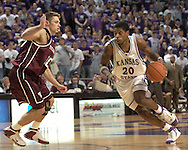 Kansas State's Cartier Martin (R) drives toward the basket, against pressure from Texas A&M's Chris Walker (L) during the second half of K-State's 58-54 win over the Aggies at Bramlage Coliseum in Manhattan, Kansas, January 18, 2006.