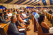 """12 JULY 2012 - FT DEFIANCE, AZ:  People pray in the main tent at the 23rd annual Navajo Nation Camp Meeting in Ft. Defiance, north of Window Rock, AZ, on the Navajo reservation. Preachers from across the Navajo Nation, and the western US, come to Navajo Nation Camp Meeting to preach an evangelical form of Christianity. Evangelical Christians make up a growing part of the reservation - there are now more than a hundred camp meetings and tent revivals on the reservation every year. The camp meeting in Ft. Defiance draws nearly 200 people each night of its six day run. Many of the attendees convert to evangelical Christianity from traditional Navajo beliefs, Catholicism or Mormonism. """"Camp meetings"""" are a form of Protestant Christian religious services originating in Britain and once common in rural parts of the United States. People would travel a great distance to a particular site to camp out, listen to itinerant preachers, and pray. This suited the rural life, before cars and highways were common, because rural areas often lacked traditional churches.    PHOTO BY JACK KURTZ"""