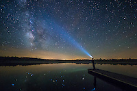 The stars of the milky way galaxy are reflected in a calm pond outside of Keosauqua, Iowa. Southeast Iowa has some of the darkest skies in the Midwest, perfect for stargazing. In this self portrait, I stood on the end of a dock and pointed my headlamp towards the stars. Because it was a humid night with fog moving across the water, the beam of light showed up well.<br />