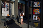 With a further 154 UK covid deaths reported in the last 24hrs, bringing the total to 43,081 victims during the Coronavirus pandemic, the easing of government lockdown restrictions for the re-opening of shops continues and the two metre social distance rule has been reduced to 'one metre plus' although a younger generation have largely ignored these distances. A boy and girl embrace outside a watch shop, near phone kiosk sex industry cards, on 24th June, in London, England.