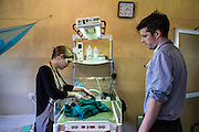 Dr Siobhan Neville and Dr Peter O'Reilly examine a very sick baby who has just been delivered by cesarian section, NICU (Neonatal Intensive Care Unit) ward. St Walburg's Hospital, Nyangao. Lindi Region, Tanzania.