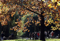 © Licenced to London News Pictures. 04/11/2013. London. UK.  <br /> General view of members of the public enjoying the autumn sun in St James' Park in London, November 4th 2013. The Woodland Trust says leaves are turning 14 days later than average, and it has been a good year for fruit and berries.<br /> Photo Credit: Susannah Ireland