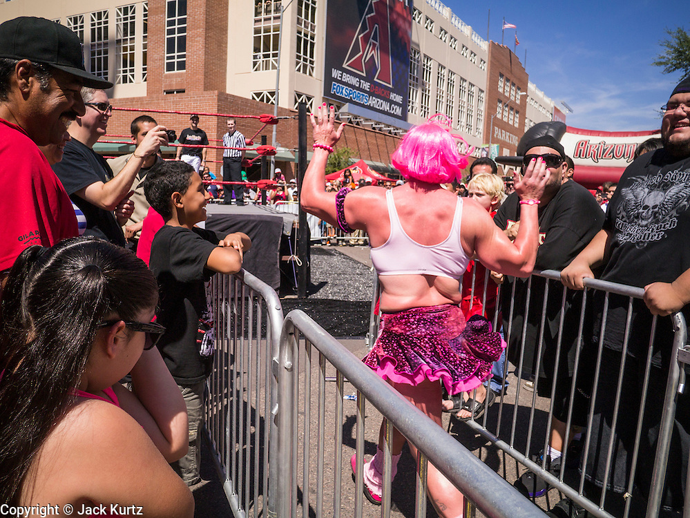 16 SEPTEMBER 2012 - PHOENIX, AZ:  CHI CHI, a Lucha Libre wrestler, runs into the ring before his Lucha Libre exhibition match on Hispanic Heritage Day. The Arizona Diamondbacks hosted their 14th Annual Hispanic Heritage Day, Sunday to kick off Hispanic Heritage Month (Sept. 15-Oct. 15) before the 1:10 p.m. game between the D-backs and San Francisco Giants. The main attraction of the Day was three Lucha Libre USA exhibition wrestling matches in front of Chase Field stadium before the game.   PHOTO BY JACK KURTZ